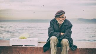 Old man sitting by the ocean